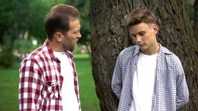 Vater, der jugendlichen Sohn, Generationskonflikt, schwieriges Alter und Missverständnis schilt stockbild