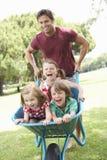 Vater, der Kindern Fahrt in der Schubkarre gibt Stockfotografie