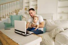 Vater, der an Laptop zu Hause arbeiten babysittet lizenzfreies stockbild