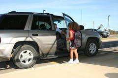 Vater, der Mädchen in SUV aufhebt Stockbild