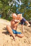 Vater, der mit Kind am Strand spielt lizenzfreie stockbilder