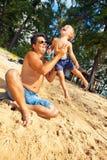 Vater, der mit Kind am Strand spielt Stockfotografie