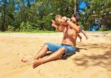 Vater, der mit Kind am Strand spielt Stockfoto