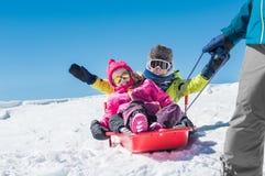 Vater, der mit Kindern auf Schnee spielt Lizenzfreies Stockbild