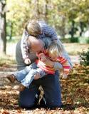 Vater, der mit Kindern im Herbstpark spielt Lizenzfreie Stockbilder