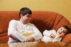 Vater, der mit Tochter auf Sofa sitzt lizenzfreie stockbilder