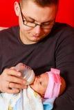 Vater, der neugeborenes Baby mit Milchflasche einzieht Stockbild