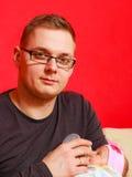 Vater, der neugeborenes Baby mit Milchflasche einzieht Lizenzfreie Stockfotos
