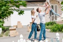 Vater, der oben Tochter während Mutterstellung nah vor ihrem neuen aufzieht stockfotografie