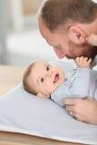 Vater, der sein lächelndes Baby streichelt Stockfoto