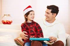Vater, der sein Sohngeschenk am Weihnachten gibt Lizenzfreie Stockfotos