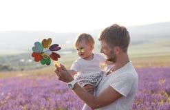 Vater, der seine kleine nette Tochter hält stockbilder