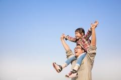 Vater, der seine Tochter auf Schultern trägt Lizenzfreie Stockfotos