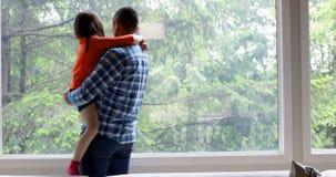 Vater, der seine Tochter bei nahe Fenster 4k zu Hause stehen hält stock video footage