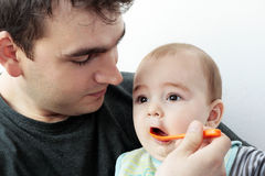 Vater, der seinem Schätzchen Nahrung gibt Stockbilder