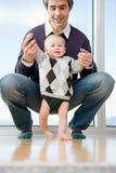 Vater, der seinem Sohn hilft zu gehen stockfotografie