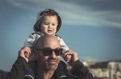 Vater, der seinen kleinen Sohn trägt lizenzfreie stockbilder