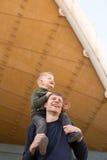 Vater, der seinen Sohn auf Schultern trägt stockfotografie