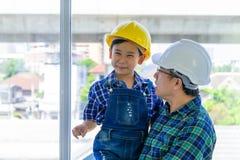 Vater, der seinen Sohn mit der Technik des schützenden Hutes für Vatertagskonzept hält stockfoto