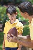Vater, der seinen Sohn unterrichtet, amerikanischen Fußball zu spielen Lizenzfreie Stockbilder