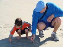 Vater, der seinen Sohn unterrichtet zu schreiben Stockbilder