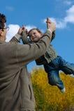 Vater, der seinen Sohn wirbelt Lizenzfreie Stockfotos