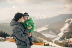 Vater, der seinen Sohn zu den Winterlandschaften trägt Lizenzfreies Stockfoto