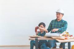 Vater, der sicher seinen Sohn unterrichtet, den Schraubenzieher zu benutzen, um das Holz zu bearbeiten lizenzfreie stockfotos