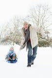 Vater, der Sohn auf Schlitten durch Schnee zieht Stockfotos