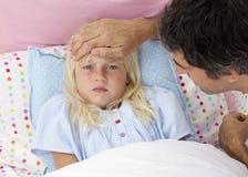 Vater, der Temperatur seiner Tochter im Bett nimmt Lizenzfreie Stockfotografie