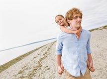 Vater, der Tochterdoppelpolfahrt am Strand gibt Stockbild