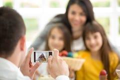 Vater, der zu Hause Familie durch Smartphone fotografiert Lizenzfreie Stockfotografie