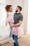 Vater, der zu Hause kleine Afroamerikanertochter in Ballettröckchentulle-Rock in den Händen hält Lizenzfreie Stockfotos