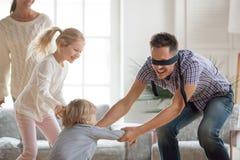 Vater, der zu Hause Versteckenspiel mit Kindern spielt Lizenzfreies Stockbild