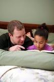 Vater, der zur Tochter liest Stockfoto