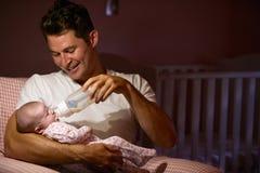 Vater-Feeding Baby With-Flasche in der Kindertagesstätte Lizenzfreies Stockfoto