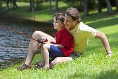 Vater-Fischen mit seinem Sohn auf einem Fluss Lizenzfreie Stockfotos