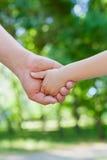 Vater hält die Hand eines kleinen Kindes im sonnigen Park, vereinigtes Familienkonzept im Freien lizenzfreie stockbilder