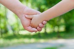Vater hält die Hand eines kleinen Kindes im sonnigen Park, vereinigtes Familienkonzept im Freien stockbild