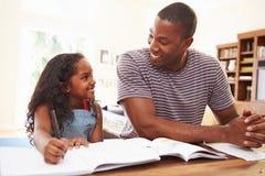 Vater-Helping Daughter With-Hausarbeit Lizenzfreies Stockbild