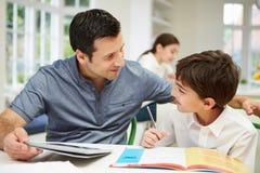 Vater-Helping Son With-Hausarbeit unter Verwendung eines Tablets Stockfoto