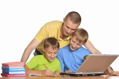 Vater hilft Kindern mit Hausarbeit Stockfotos