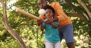 Vater hilft seinem Sohn, Baseball zu spielen stock footage