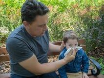 Vater hilft seinem Sohn, seine Nase durchzubrennen stockfotos
