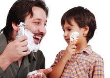 Vater ist, seinem Jungen beibringend, wie man rasiert Stockfotos