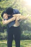 Vater küsst seinen Sohn im Park Stockbild