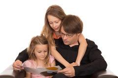 Vater las ein Buch mit seinen Töchtern Lizenzfreies Stockbild