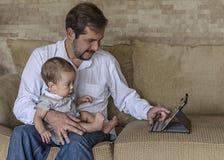 Vater mit dem Babysohn, der Tabletten-PC verwendet Lizenzfreie Stockbilder