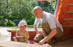 Vater mit dem Kleinkind, das im Sandkasten spielt Stockfoto