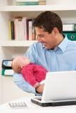 Vater mit dem neugeborenen Schätzchen, das vom Haus arbeitet Stockbild